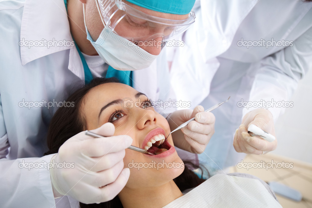 Dentist and his assistant carrying out a thorough examination — Stock Photo #10733789