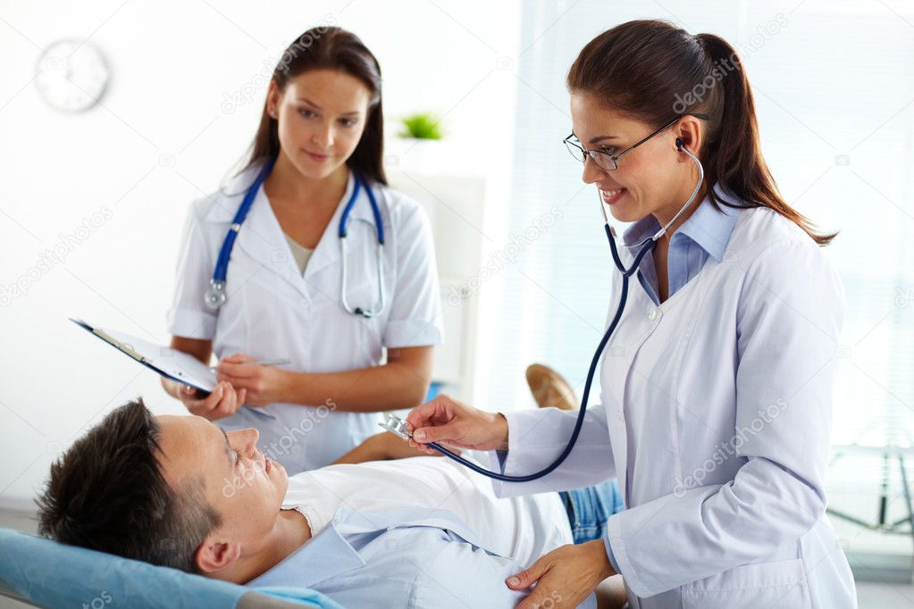 Portrait of two female doctors looking at patient during medical treatment in hospital — Stock Photo #10733795