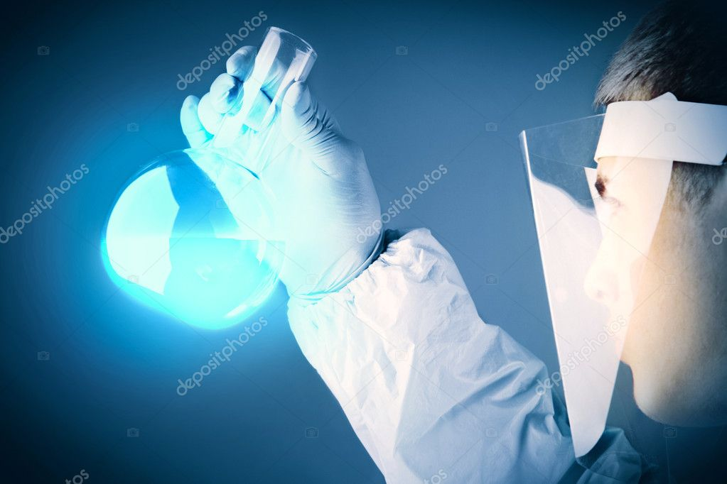 Young scientist in transparent protective mask looking at blue substance poured in a flask — Stock Photo #10733827