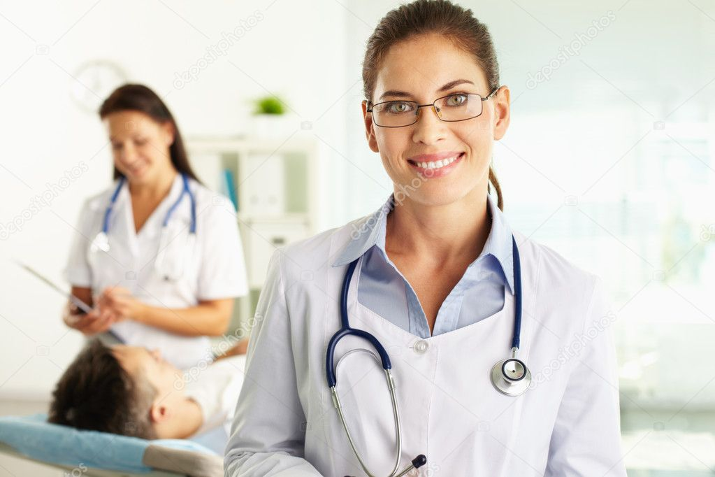 Portrait of a friendly physician smiling at camera, nurse and patient can be seen in background — Stock Photo #10733837
