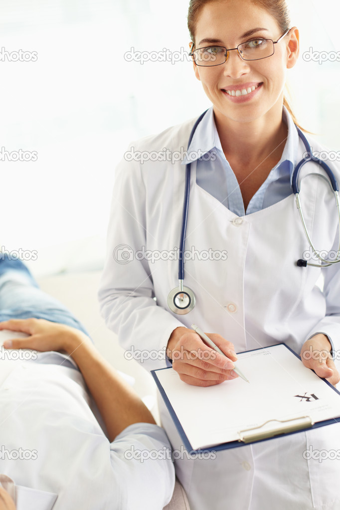 Portrait of a positive doctor holding the clipboard with an attached blank  Stock Photo #10733849