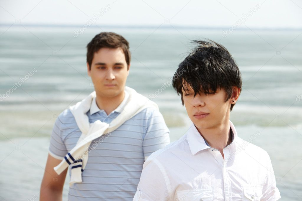 Romantic gay couple standing together on a windy beach — Stock Photo #10734428