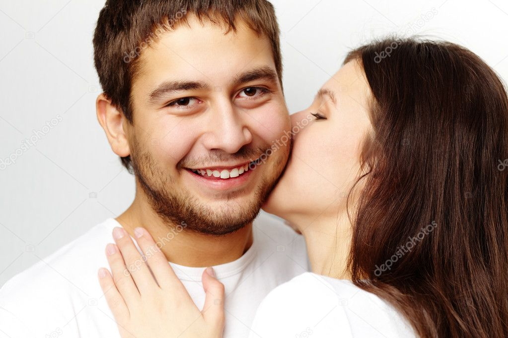 Happy girl kissing her boyfriend while he looking at camera — Stock Photo #10734916