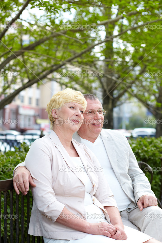 Mature couple sitting on bench in park in summer  Stock Photo #10735090