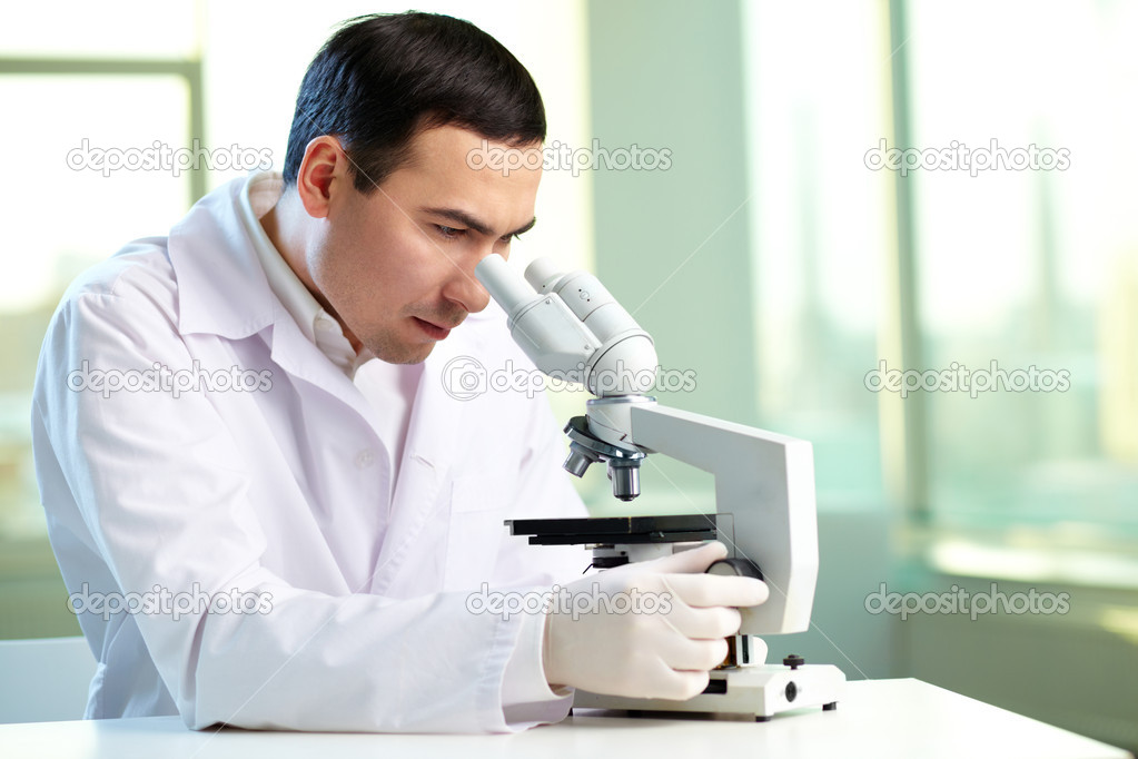 Serious clinician studying new substance in laboratory — Stock Photo #10735145