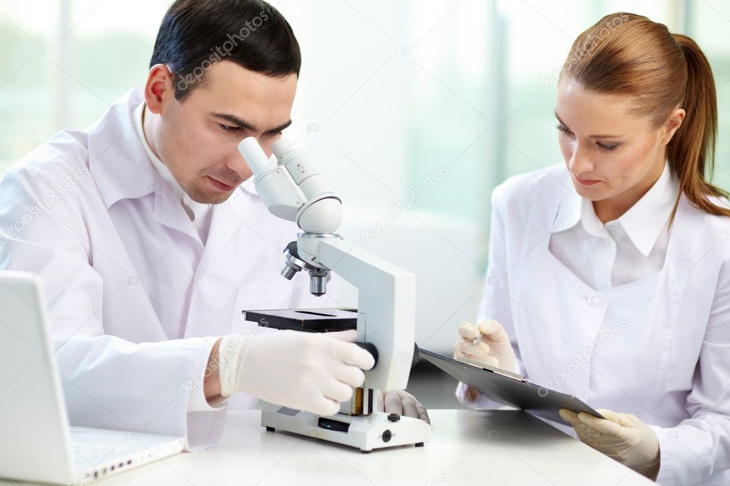 Serious clinicians studying chemical elements in laboratory  Stock Photo #10735147