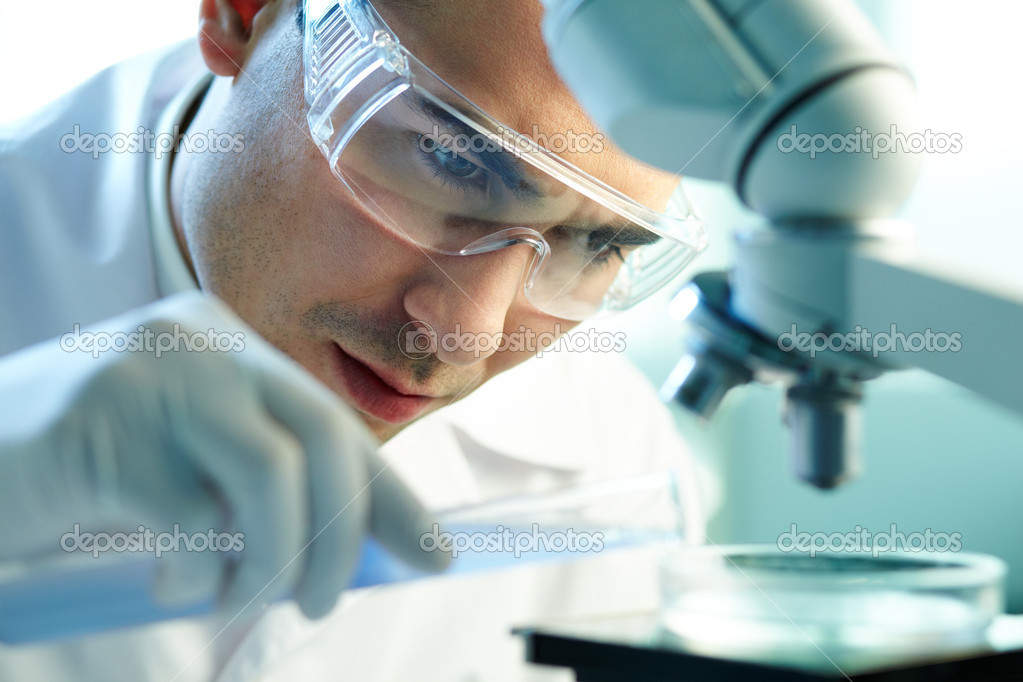 Serious clinician studying chemical element in laboratory — Stock Photo #10735153