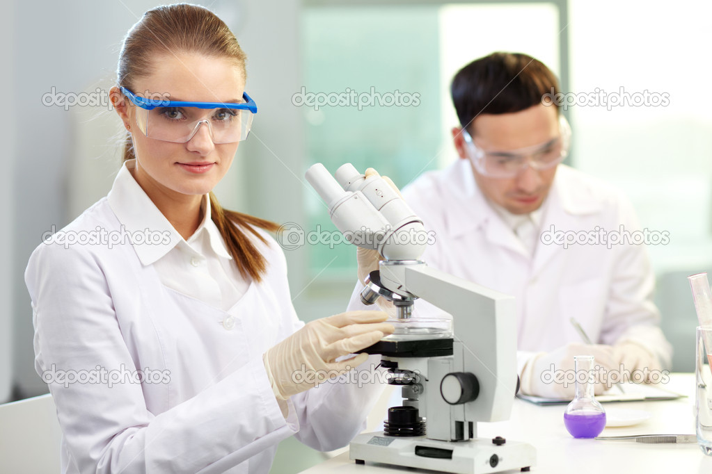 Pretty clinician with microscope looking at camera in laboratory — Stock Photo #10735160