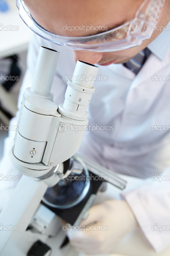 Male scientist in protective eyeglasses looking through the microscope — Stock Photo #10735178
