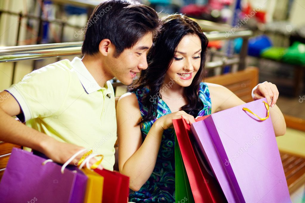 Young woman and her boyfriend looking in the shopping bag with sweet anticipation — Photo #10745103