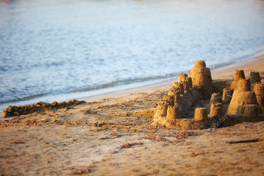 Castle made of wet sand standing on the beach at sunset — Stock fotografie #10745451