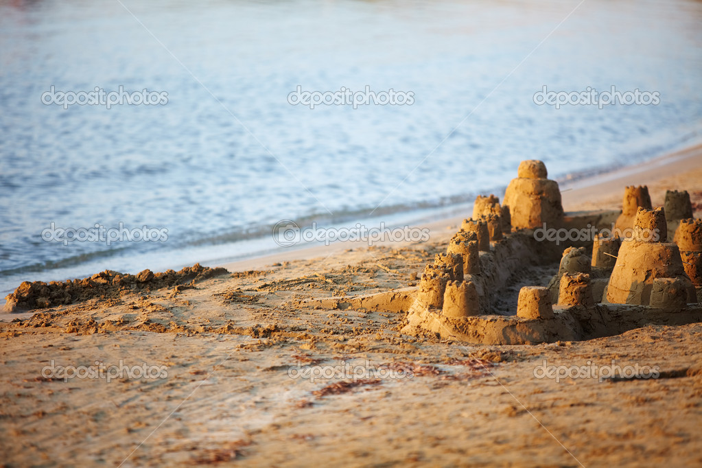 Castle made of wet sand standing on the beach at sunset — Zdjęcie stockowe #10745451