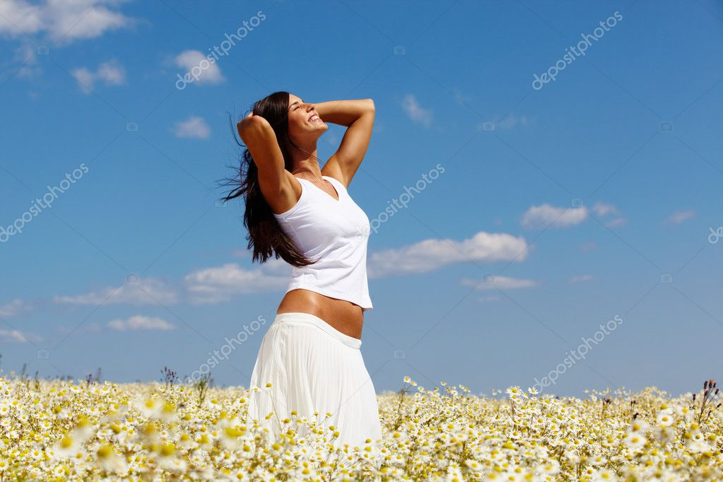 Young woman in white standing among chamomiles on a sunny day — Stock Photo #10745751