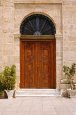 Ancient wooden door with arched window above — Stock Photo