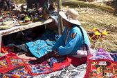 Peruvian woman selling souvenirs on floating island — Stock Photo