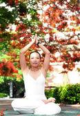 Yoga exercise under blooming flame trees — Stock Photo
