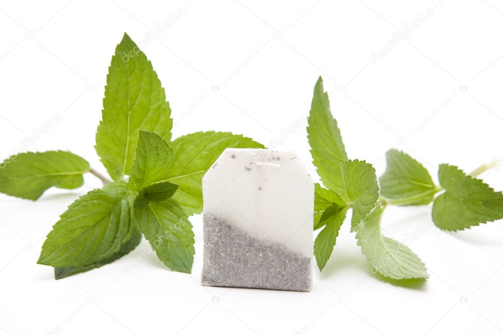 Tea bag and peppermint leaves on white background — Stock Photo #10656647