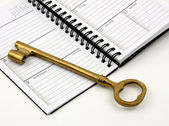 Golden Key On A Daily Planner — Stock Photo