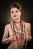 Young beautiful woman with beads and jewelry — Stock Photo
