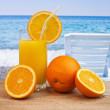 Glass of orange juice on a beach