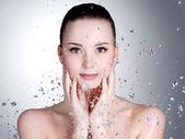 Kapky vody po celém obličeji krásná žena