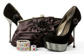 Sexy fashionable shoes, golden jewelry and handbag isolated on white background.