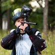 Постер, плакат: Paintball shooter aiming the gun