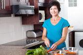 Attraente donna invecchiata centrale cottura in cucina