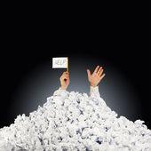 Persona sotto stropicciata pila di carte con la mano che tiene un segno di aiuto