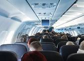 Cestující v interiéru kabiny letadla