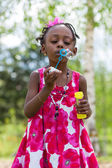 Cute african american little girl blowing soap bubbles