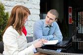 Obchodní partneři setkání: samec a samice s notebookem sedět venku