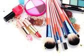 Make-up štětce v držáku a kosmetiky izolovaných na bílém