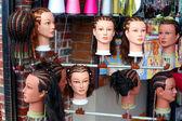 Assortiti acconciature intrecciate sulle teste di manichino visualizzate allesterno di un negozio