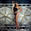 Постер, плакат: Sexy top model in lingerie on a stage with huge turbo fan behind