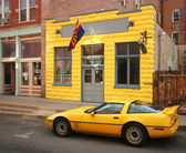 Una macchina sportiva gialla davanti a un edificio giallo
