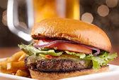 Cheeseburger gourmet con boccale di birra in sottofondo