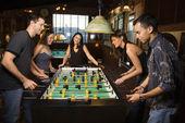 Gruppo di giovani uomini e donne, godendo di una partita di calcio balilla in un bar. tiro orizzontale