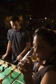 Giovane donna bevendo birra e guardando visualizzatore mentre uomo gioca calcio balilla nel pub