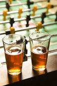 Due bicchieri di birra sul tavolo di calcio balilla