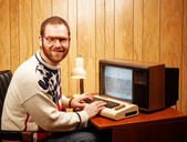 Handsome Nerdy Adult using a Vintage Computer TV