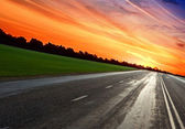 Empty blurry road under sunset light with clouds