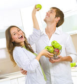 Happy Couple Eating fresh fruits.Having fun on a kitchen.Dieting