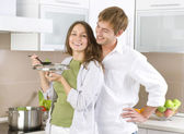 Young happy couple cooking together at home kitchen