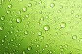 Přes zelené kapky vody. closeup