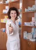 Junge Apothekerin zeigt Flasche mit Pillen