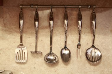 Set of kitchen utensils hanging on the wall