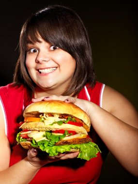 Woman holding big hamburger.
