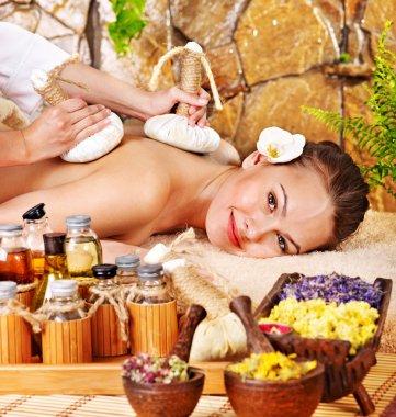 Woman getting thai herbal compress massage .