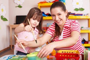 Child with teacher in preschool.
